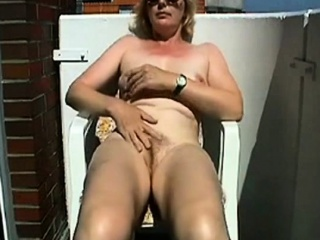 Mature tugging on the balcony